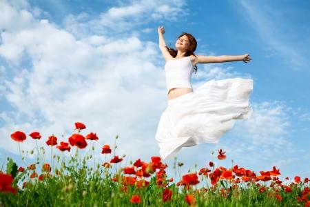 jumping: mujer de belleza en el campo de amapolas en vestido blanco Foto de archivo