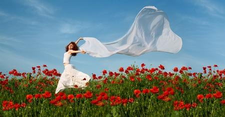 campo de flores: mujer de belleza en el campo de amapolas con tejido blanco bajo cielo