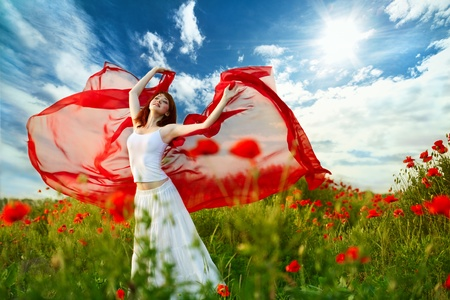 beauty woman in poppy field with red tissue under sky Stock Photo