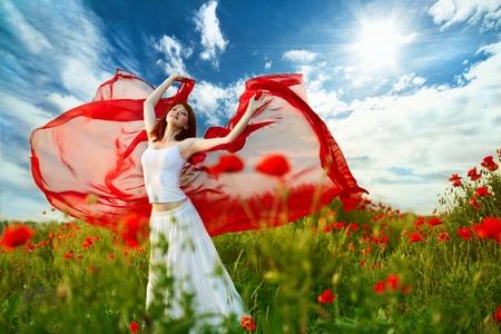 beauty woman in poppy field with red tissue under sky Standard-Bild