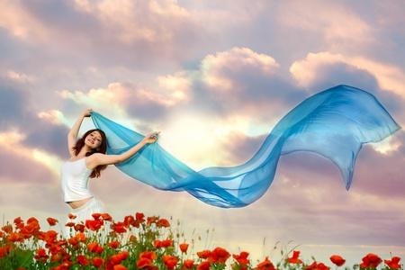 shawl: schoonheid vrouw in papaverveld met blauwe weefsel onder hemel Stockfoto