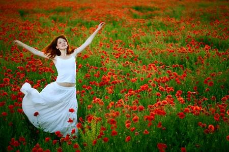 beauty woman in white dress running poppy field