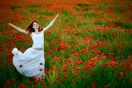 poppy field: schoonheid vrouw in witte jurk loopt papaverveld