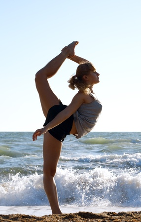 Beautiful young woman doing fitness exercise on a beach photo