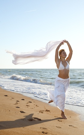 woman running on the sea beach with white scarf Stock Photo - 9759360