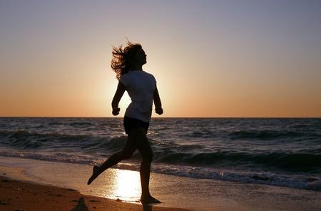 silhouette girl run on sea coast in sunset photo