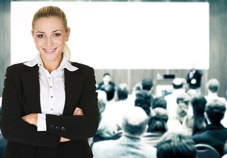 speaker: woman over conference hall full of people participating in the business training. Stock Photo