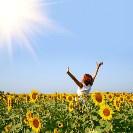 sunflowers field: beauty redhaired woman in sunflower field