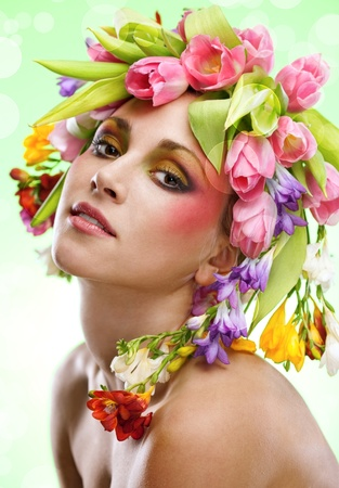 beauty woman portrait with wreath from flowers on head green background photo