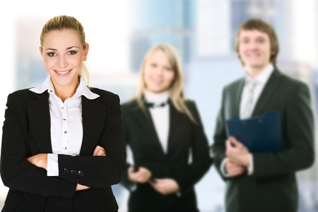 Business woman in an office environment with team photo