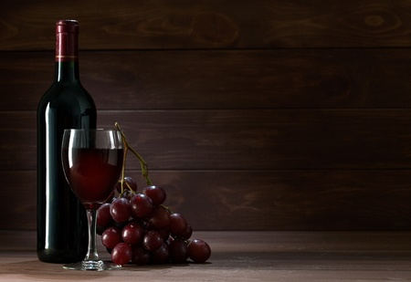 wine and grapes: bottle of wine in the cellar of  wooden Stock Photo