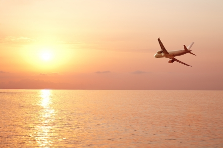 above the clouds: airplane fly over sea and sunset Stock Photo