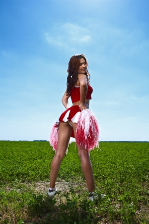 beauty cheerleader on field under blue sky Stock Photo