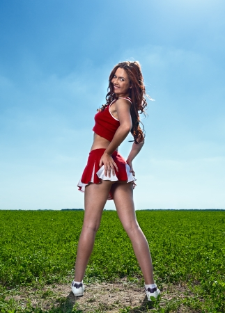 beauty cheerleader on field under blue sky photo