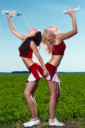two beauty cheerleaderr on field under blue sky photo