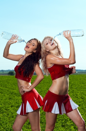 sexy school girl: beauty cheerleader with water on field under blue sky Stock Photo