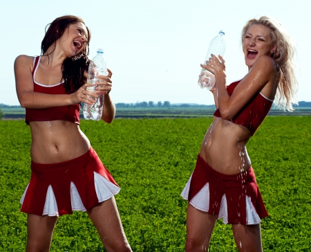 wet body: beauty cheerleader with water on field under blue sky Stock Photo