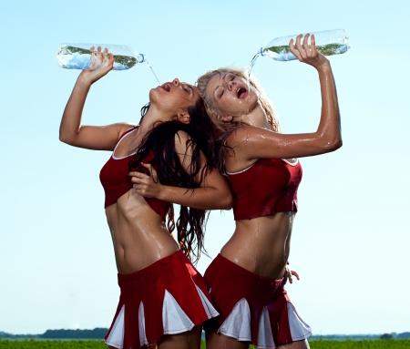 schoonheid cheerleader met water op veld onder blauwe hemel