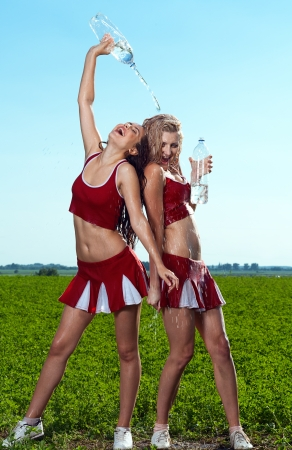 beauty cheerleader with water on field under blue sky photo