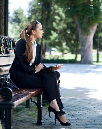 businesswoman on bench in park
