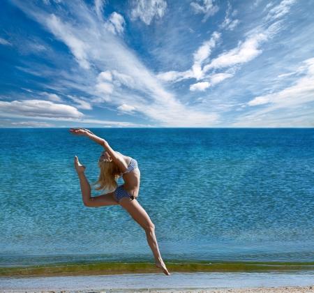 schoonheid sportieve vrouw doet oefeningen op het strand Stockfoto