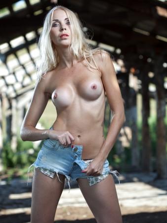 Bella ragazza in topless in un vecchio fienile