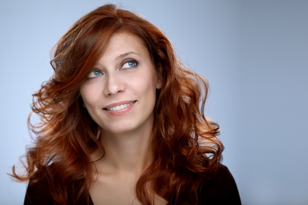 portrait of beautiful woman redhair on gray photo