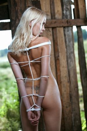 Beautiful girl tied in an old barn