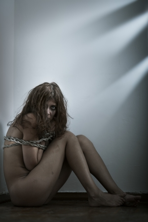 naked body: redhaired woman bondage on gray background