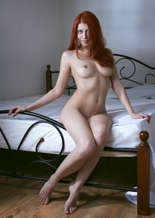female nudity: Naked girl sitting on the bed