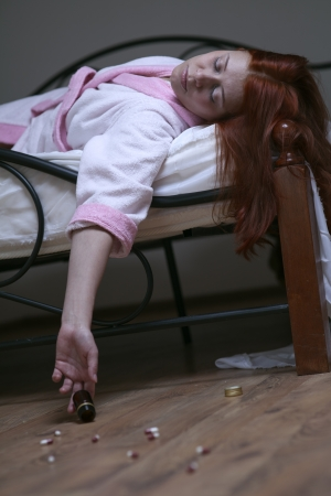 overdosering: roodharige vrouw in bed overdosis tablet Stockfoto