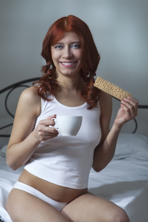 beauty woman drink coffee and eat toast in bed photo