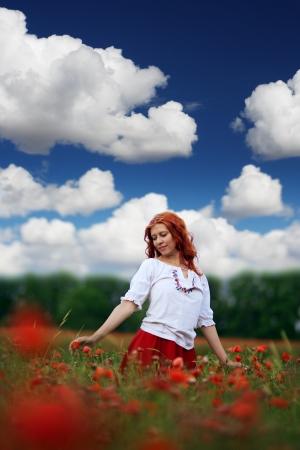 beauty red headed woman in poppy field