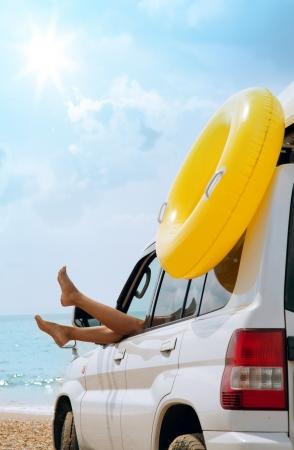 vrouw benen in de auto-venster op zee strand Stockfoto