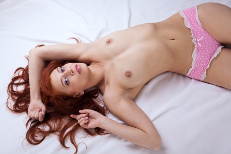 sexy redhead young woman on the bed