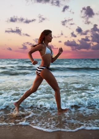girl runs along the shore of the sea photo