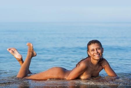 nue plage: Fille se baigner nue dans la mer