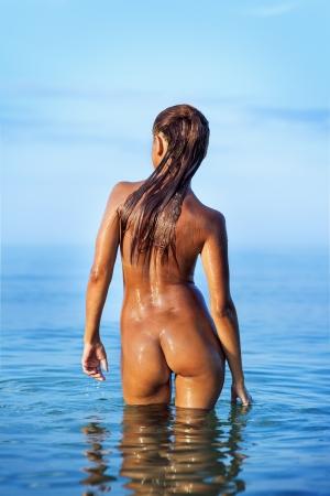 mujer desnuda de espalda: Muchacha que se ba�a desnuda en el mar