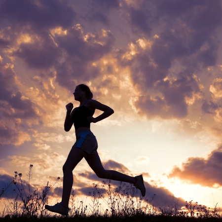 marathon: Silhouette woman run under blue sky with clouds and sun Stock Photo