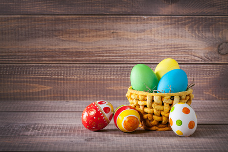 easter color eggs in basket on wooden
