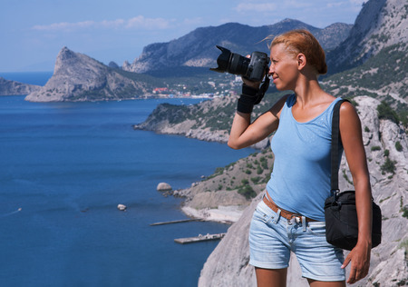 beauty woman photographer on rock at sea