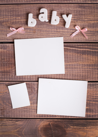 word baby and white frame photo on wood background photo