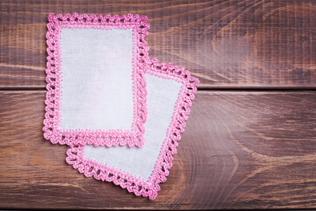 Napkin with pink lace on the wooden background  photo