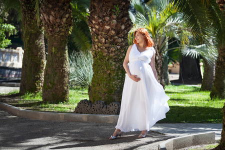 maternity leave: Pregnant woman white dress in the park
