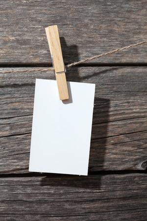 attach: papel blanco en las patas en el fondo de madera Foto de archivo