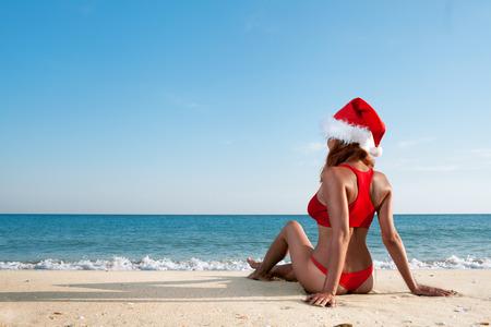 bikini island: sexy woman in santa hat on sea beach Stock Photo