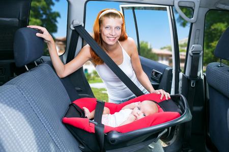 cinturón de seguridad: asientos bebé de la mujer en el asiento de coche