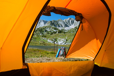 view to outside: camping in mountain lake with backpack and  Nordic walking sticks