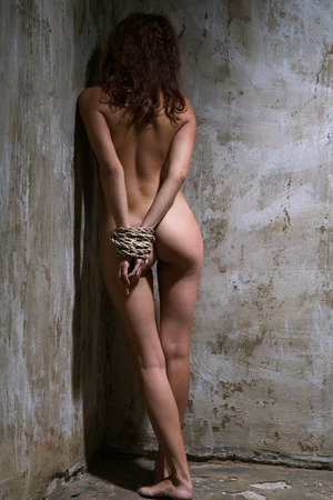 girls naked: naked red-haired woman tied with a rope in the old shabby room Stock Photo