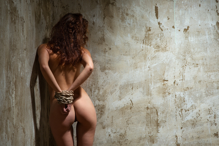naked red-haired woman tied with a rope in the old shabby room Stock Photo